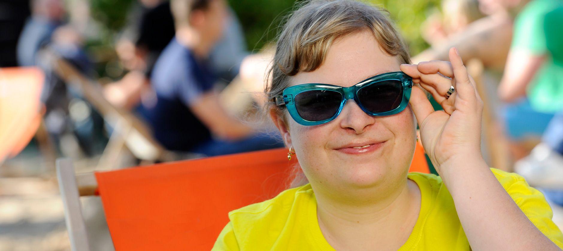 Frau mit Sonnenbrille im Liegestuhl